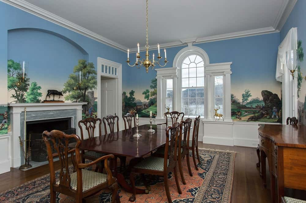 This dining room has a dark wooden dining set surrounded by walls that are adorned with painted murals depicting trees and skies that make the white mantle of the fireplace stand out along with the arched window. Images courtesy of Toptenrealestatedeals.com.