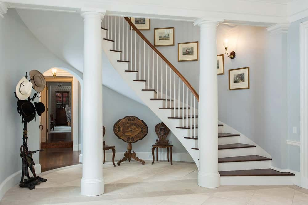 Upon entry of the house, you are welcomed by this simple and homey foyer with a couple of white pillars and a wooden sitting area underneath the spiral staircase. Images courtesy of Toptenrealestatedeals.com.