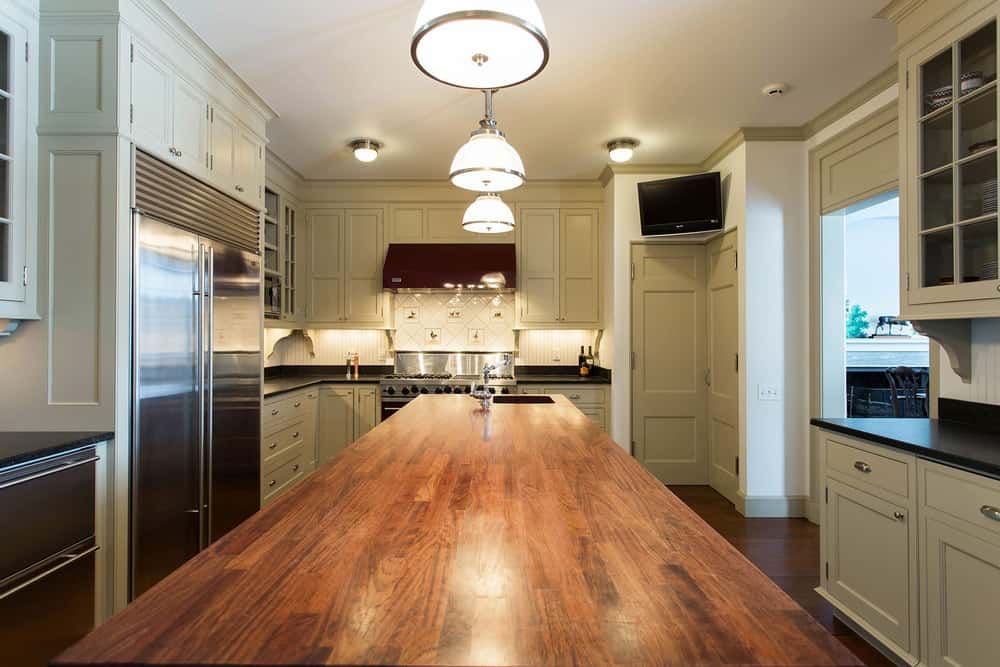This is a closer look at the butcher block countertop of the kitchen island that is topped with warm pendant lights hanging from the beige ceiling. Images courtesy of Toptenrealestatedeals.com.