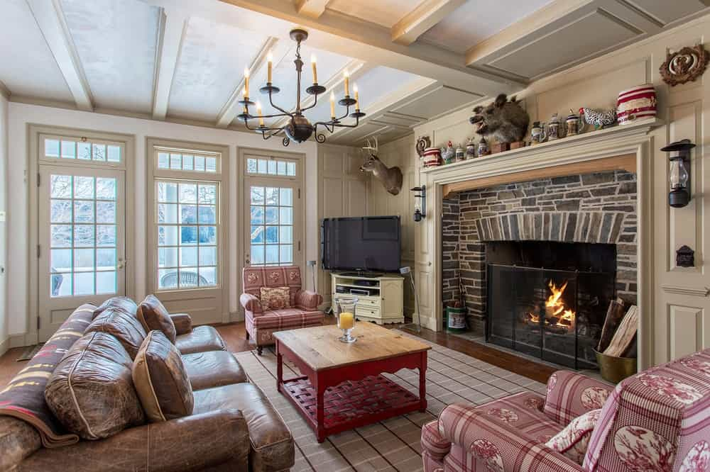 This other living room has a much homier feel to it with a large stone fireplace, beige walls and ceiling that has exposed wooden beams and a simple chandelier over the red coffee table. Images courtesy of Toptenrealestatedeals.com.