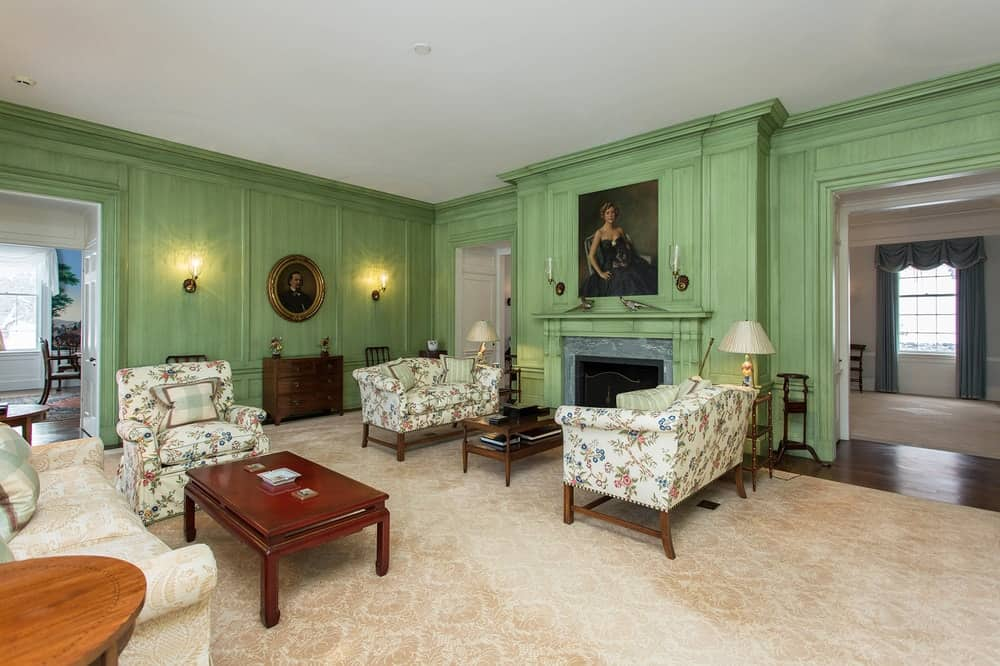 This living room has a gorgeous and charming green tone to its walls and fireplace mantle that is topped with a classic painting. The walls on the other side are also adorned with wall-mounted lamps and decors. Images courtesy of Toptenrealestatedeals.com.