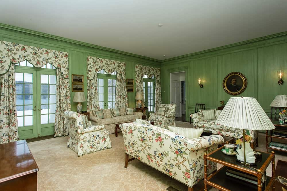This living room has beautiful floral slipcovers and upholstery for the sofas and cushioned arm chairs to match the curtains of the French glass doors on one side of the room bringing in natural lighting. Images courtesy of Toptenrealestatedeals.com.