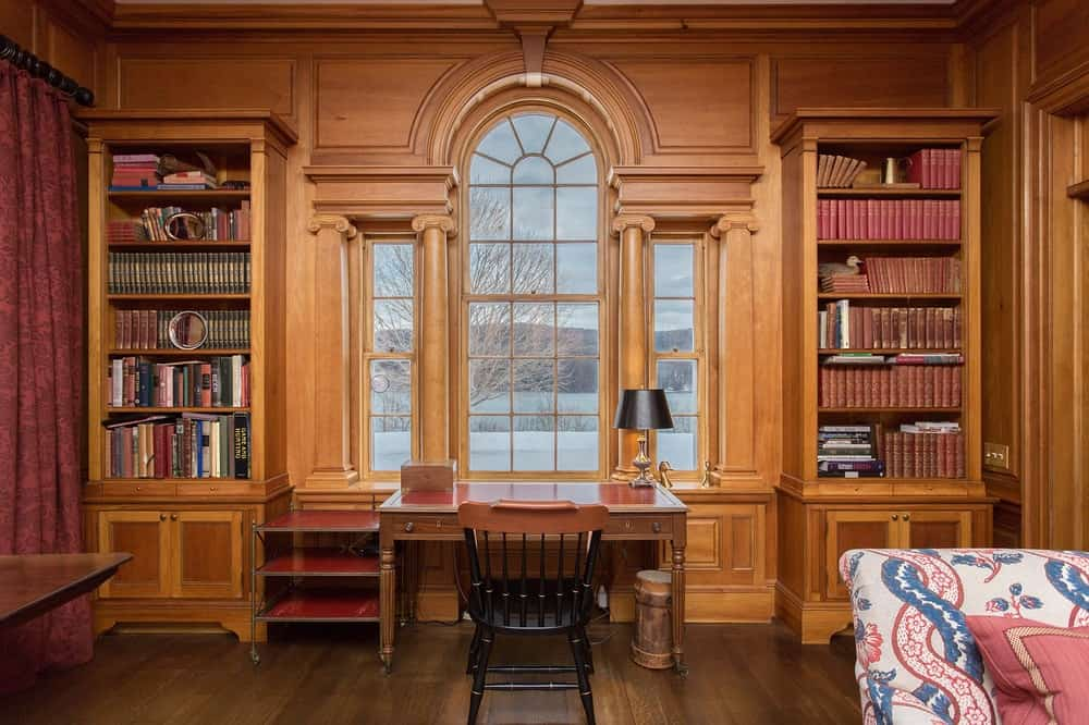 This home office has a classic elegance to its wooden walls, bookshelves, desk and the tall arched window above the wooden desk. Images courtesy of Toptenrealestatedeals.com.