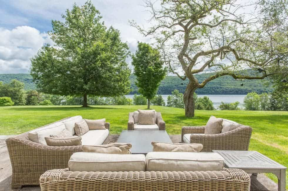This is an outdoor patio that maximizes the beauty of the lush green lawn of grass and the view of the lake along with tall trees. These give a nice background for the woven wicker sofa set with cushions paired with a coffee table. Images courtesy of Toptenrealestatedeals.com.