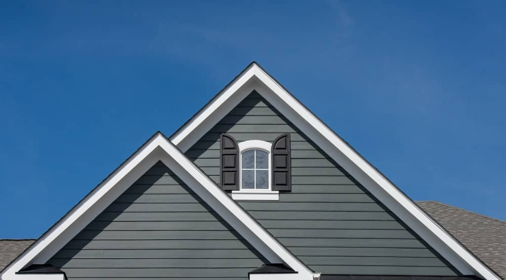 Gable with gray-blue exterior siding and an attic window with black shutter.