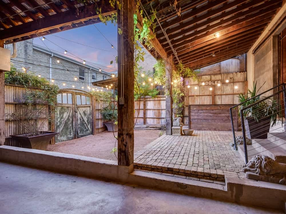 This covered area just outside of the house has rustic brick walkways paired with a tall shed wooden ceiling that has exposed beams. Images courtesy of Toptenrealestatedeals.com.