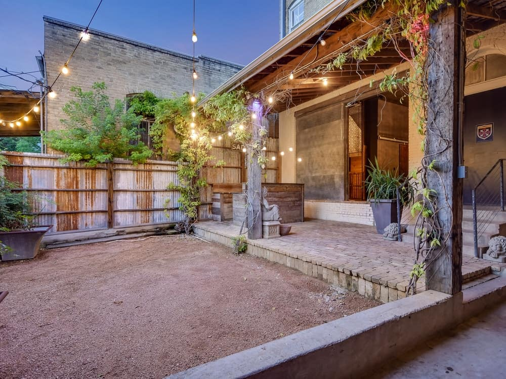 This backyard has a cozy and homey vibe to its warm rope lights and surrounding wooden elements that add to the rustic feel of the area. Images courtesy of Toptenrealestatedeals.com.