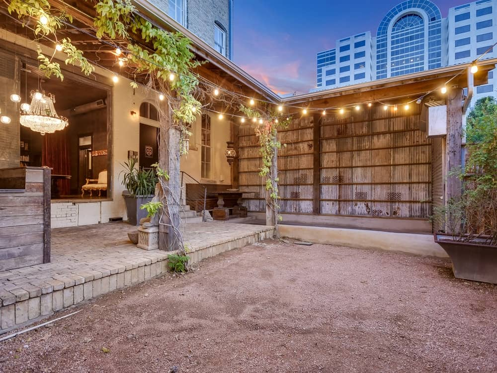 The backyard has a small open area with dirt flooring perfect for any outdoor activity under the rope lights. Images courtesy of Toptenrealestatedeals.com.