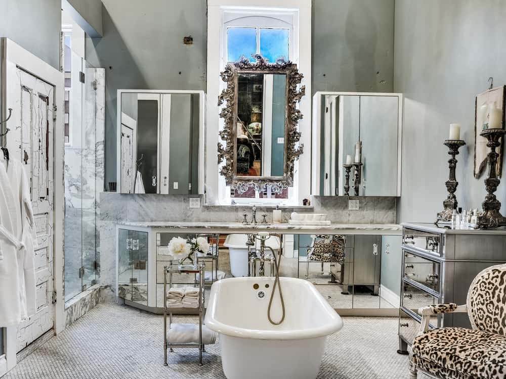 This spacious bathroom has a freestanding bathtub in the middle of the floor across from the vanity that has mirrored cabinetry to match its wall-mounted mirrors. Images courtesy of Toptenrealestatedeals.com.