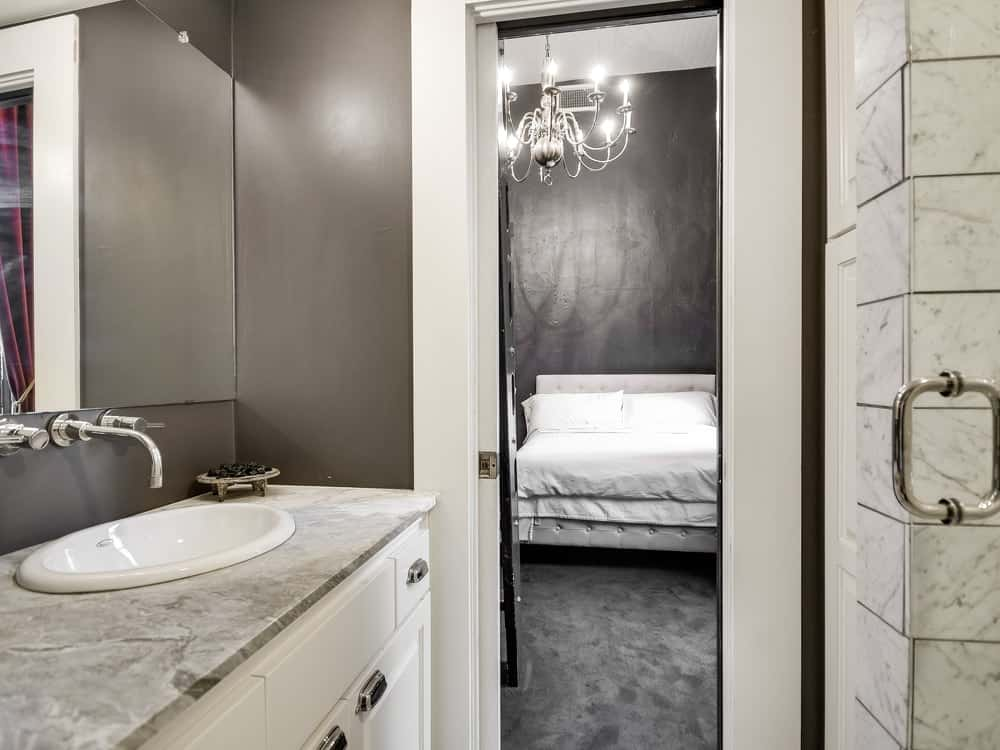 This is the bathroom beneath the second bed that can be accessed by a ladder. This bathroom has the same warm gray tone to its walls as the bedroom contrasting the white vanity. Images courtesy of Toptenrealestatedeals.com.