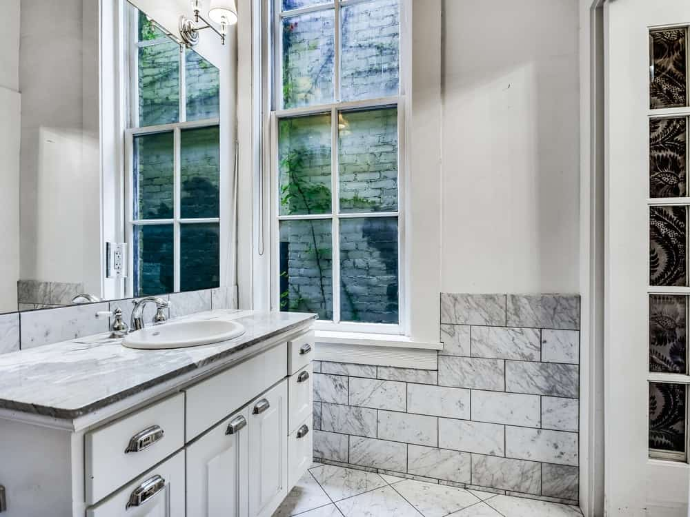 This bathroom has a white vanity area with a tall wall-mounted mirror next to the tall windows that bring in natural lighting to the light tone of the walls. Images courtesy of Toptenrealestatedeals.com.