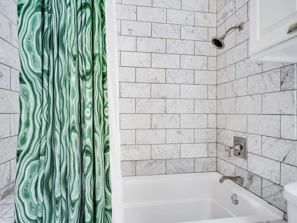 This is a closer look at the shower area of this bathroom with lovely green curtains and white tiles on its walls arranged in a brick wall look. Images courtesy of Toptenrealestatedeals.com.