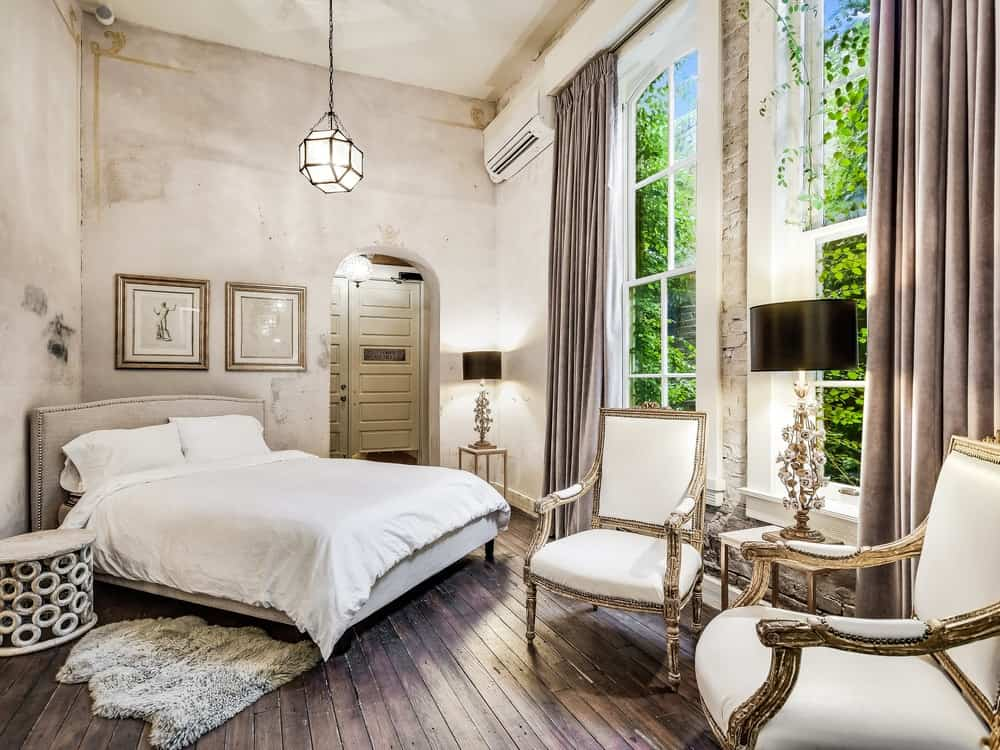 This spacious bedroom has a light tone to its walls and ceiling augmented by the natural lights coming in from the tall windows complemented by a sitting area. Images courtesy of Toptenrealestatedeals.com.