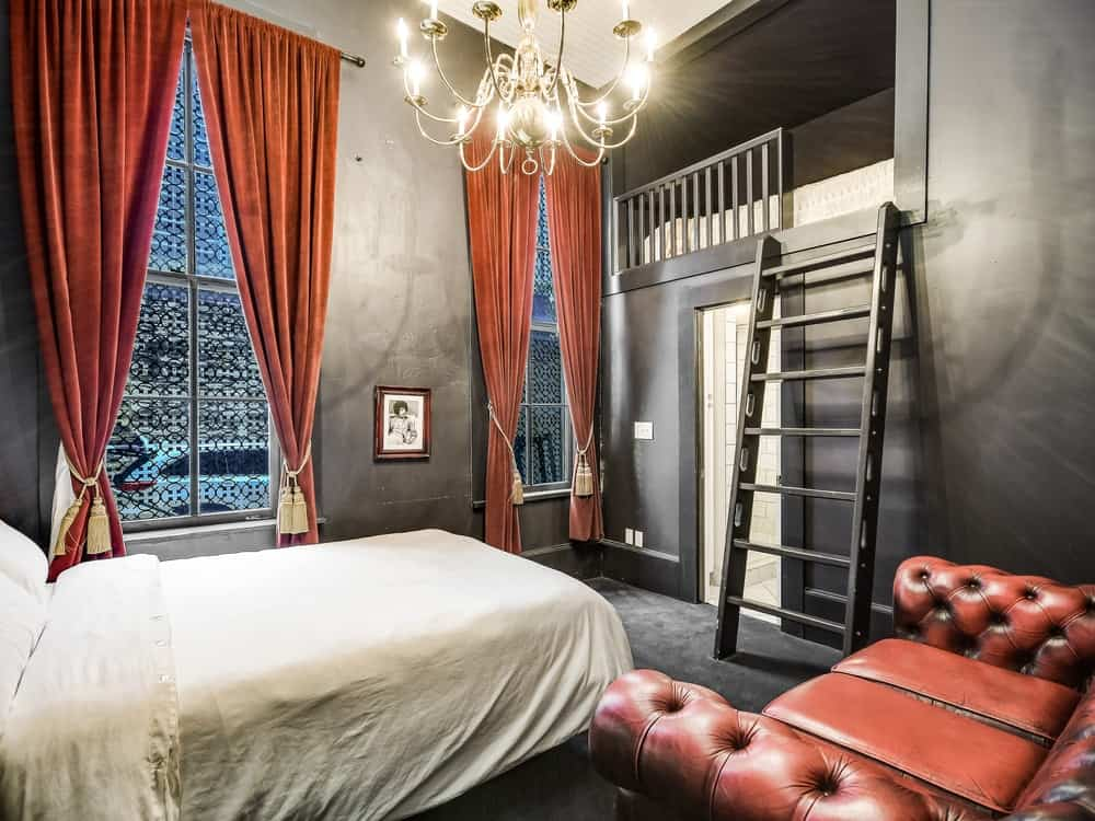 This angle of the bedroom shows that it has a second bed accessible through a ladder. This also shows the pair of tall windows with rich red curtains illuminated by the chandelier. Images courtesy of Toptenrealestatedeals.com.