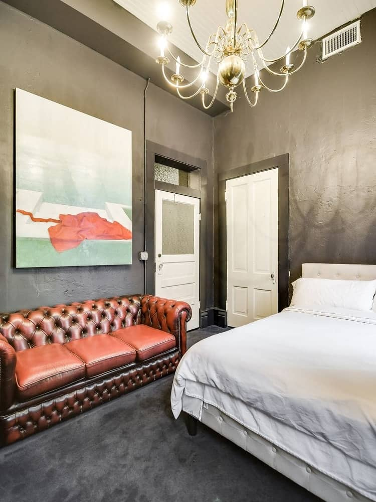 This bedroom has warm gray walls that makes the red leather couch at the side of the bed stand out along with the large wall-mounted artwork above it. Images courtesy of Toptenrealestatedeals.com.
