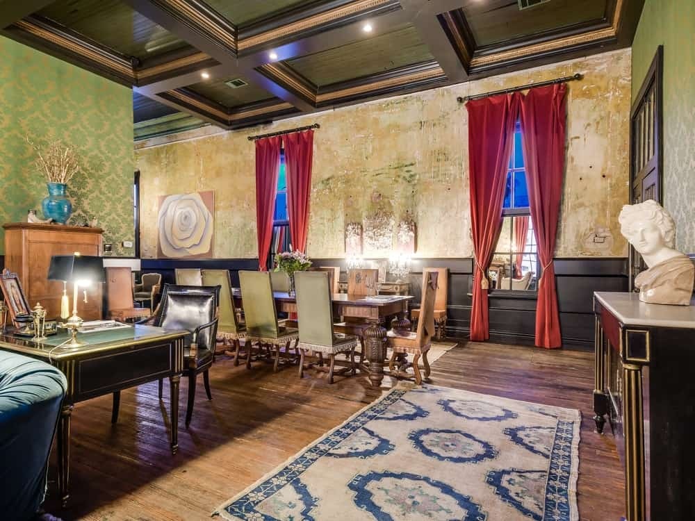 The dining area at the far end of the great room has a long wooden rectangular dining table surrounded by upholstered chairs that match the tone of the green wallpaper and the coffered ceiling with recessed lights. Images courtesy of Toptenrealestatedeals.com.