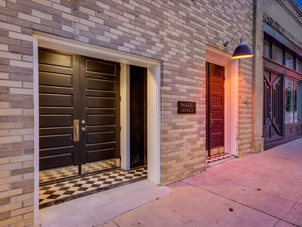 This is the rustic and charming main entry of the house made of bricks balanced by the elegant doors illuminated by the lamps. Images courtesy of Toptenrealestatedeals.com.
