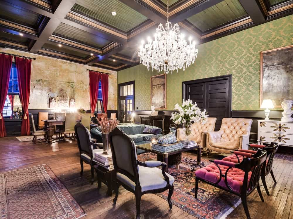 This living room is topped with a brilliant crystal chandelier that hangs from the elegant coffered ceiling with exposed dark wooden beams. Images courtesy of Toptenrealestatedeals.com.