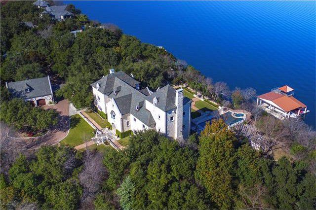 Aerial view of this mansion featuring its white exterior surrounded by the lush landscape.