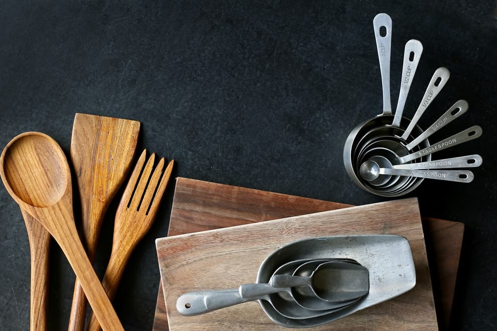 Wooden and steel baking and cooking supplies on a black background.