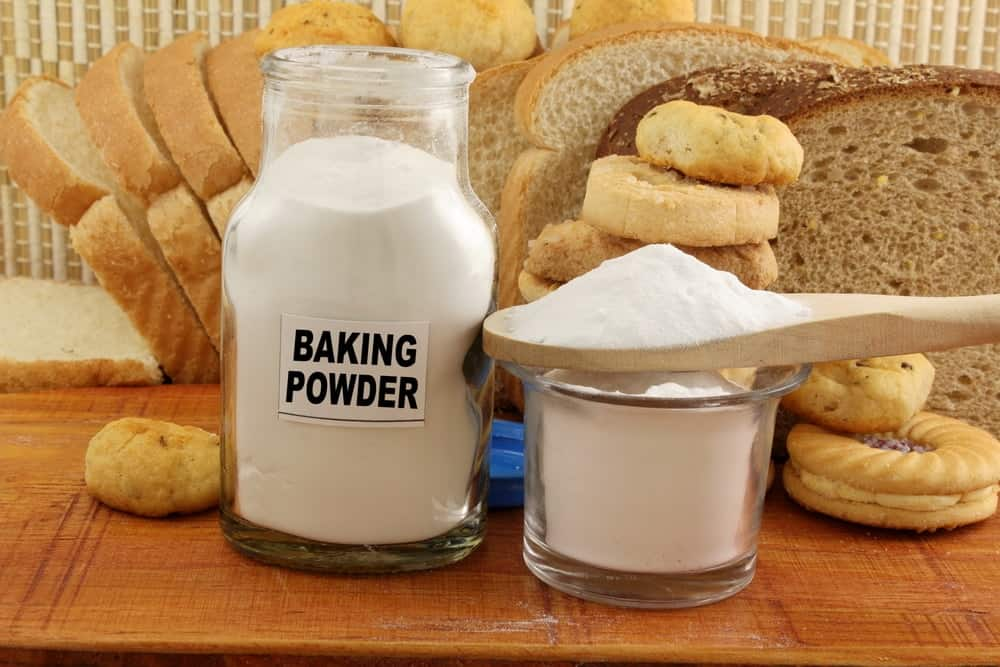 Jars of baking powder in front of loaves of bread and cookies.