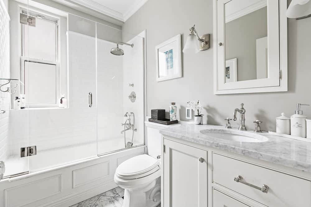 The bright white housing of the bathtub matches perfectly with the cabinetry of the vanity beside the white porcelain toilet. The bathtub housing is topped with a glass enclosure that serves as the walls of the shower area. Images courtesy of Toptenrealestatedeals.com.