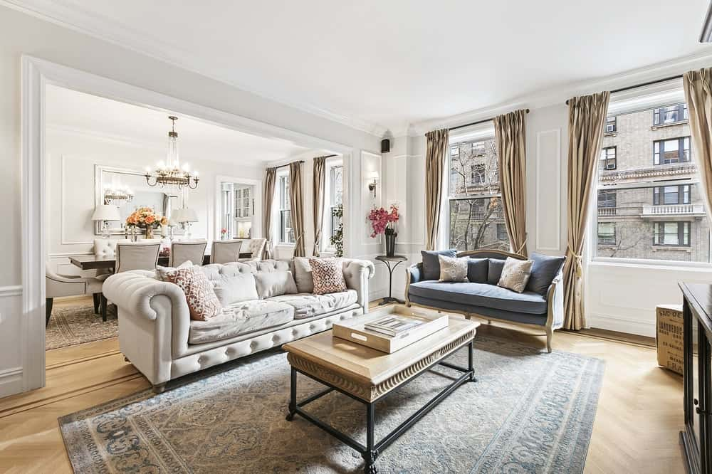 This is a bright great room that houses the living room and the dining area under one large ceiling brightened by a row of tall windows. The living room has a large cushioned beige sofa and a gray sofa beside it facing the coffee table. Images courtesy of Toptenrealestatedeals.com.