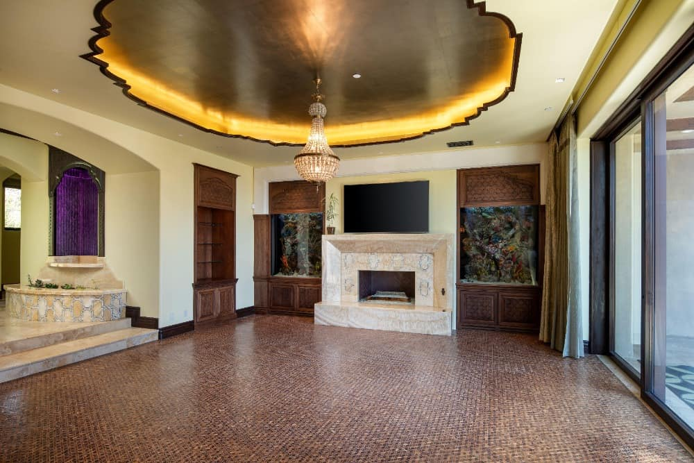A family room with stunning brown tiles flooring, a magnificent ceiling design and a fireplace and a widescreen TV on the wall. Images courtesy of Toptenrealestatedeals.com.
