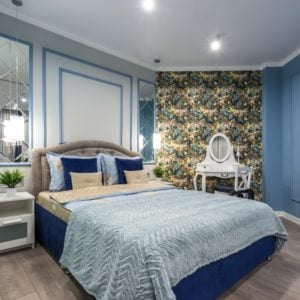 A beautiful guest bedroom with a blue bed to match the blue walls.