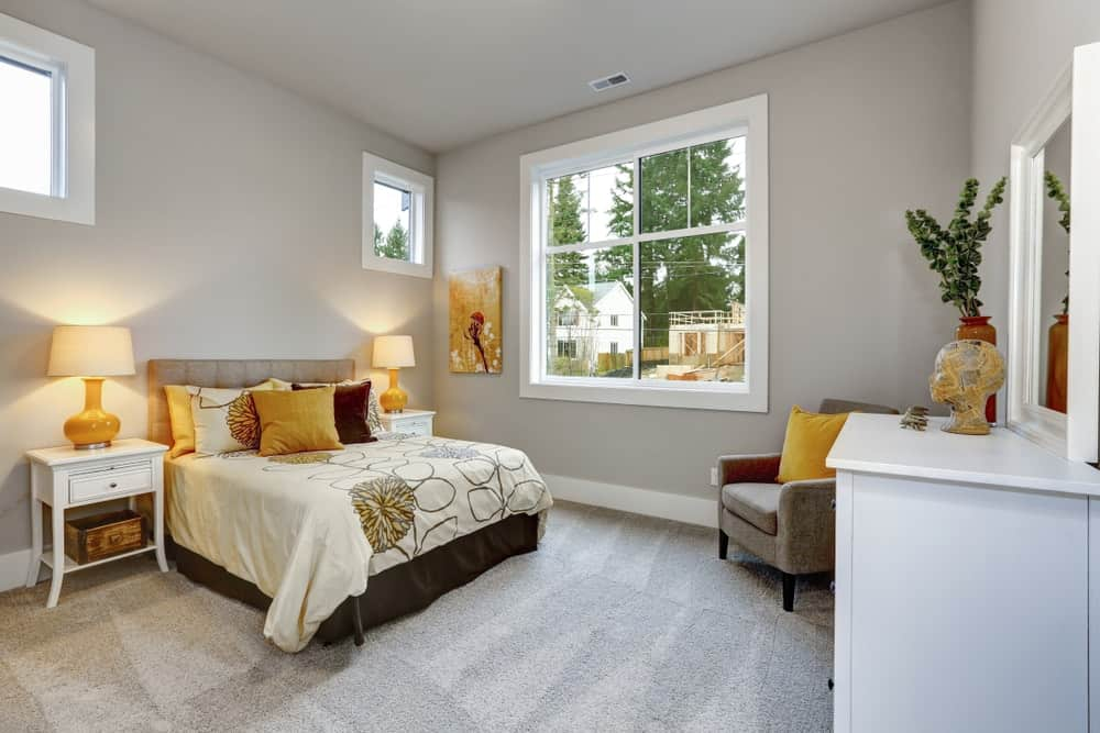 A cozy guest bedroom with gray walls.