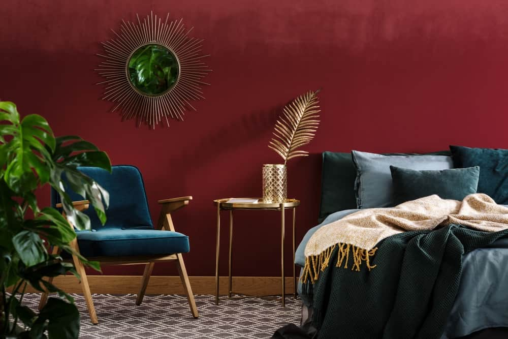A dynamic and vibrant guest bedroom complement by its deep red wall.