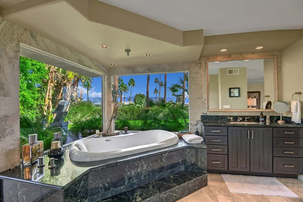 The master bathroom has a corner bathtub inlaid with the same dark marble as the countertop of the vanity beside it. The bathtub is complemented by a couple of large glass windows offering a lush and green view outside. Images courtesy of Toptenrealestatedeals.com.
