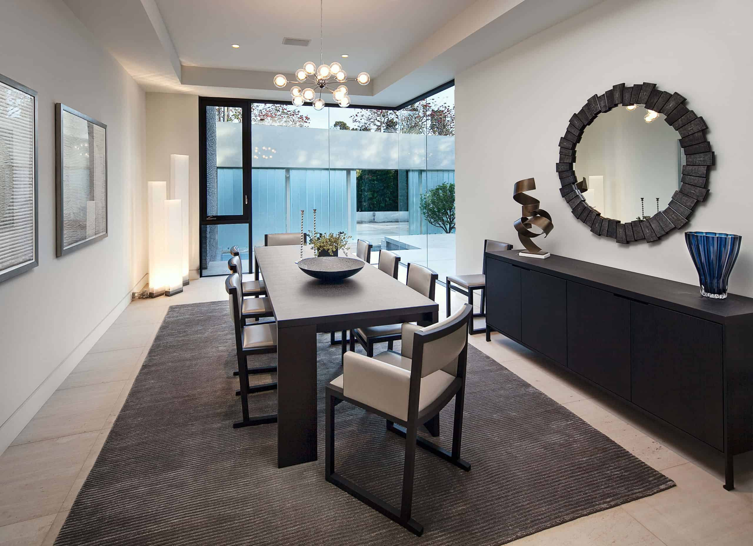 The formal dining room features elegant, lengthy dark wood table with matching cabinetry, unique art pieces scattered throughout, and pristine view toward the front courtyard.