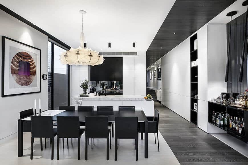 The dining and kitchen area is defined by the light marble flooring, distinct from the muted grey hardwood seen throughout the rest of the home. The high contrast look is amplified by a black dining set and white kitchen cabinetry.