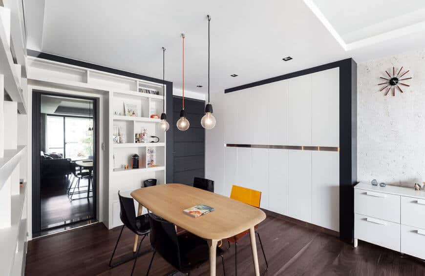The dining room space exemplifies the mixture of white and dark hues throughout the home, with the dominant lighter shade defined by contrast.