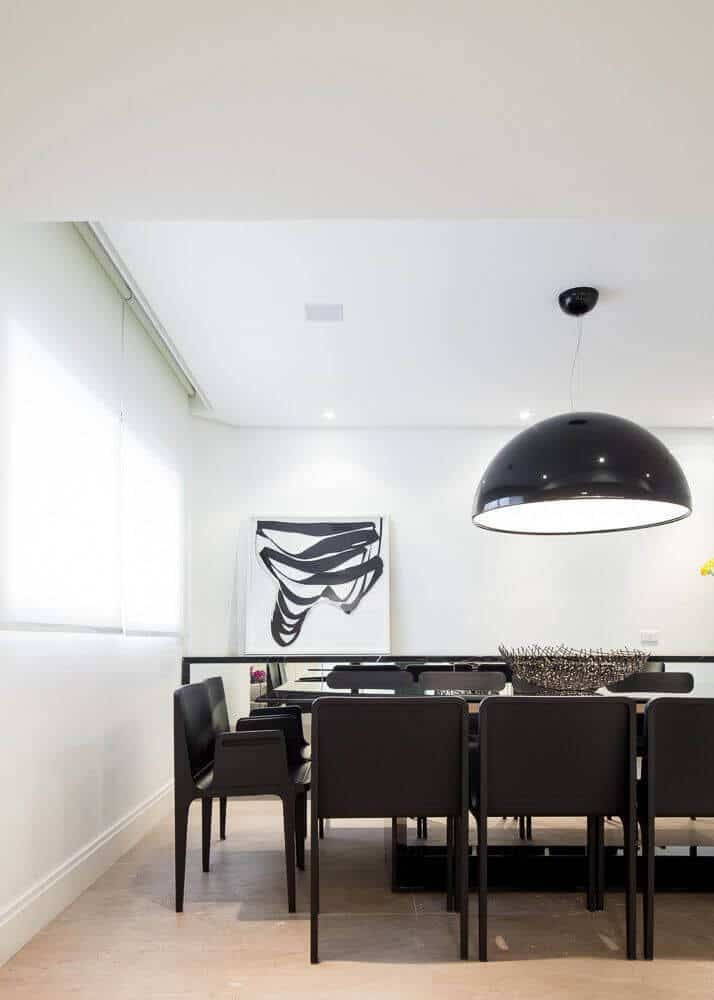 The formal dining room has light beige tile floors and crisp white walls. The modern dark wood dining set has two chairs at the heads of the tables and is perfectly sized for a family gathering.