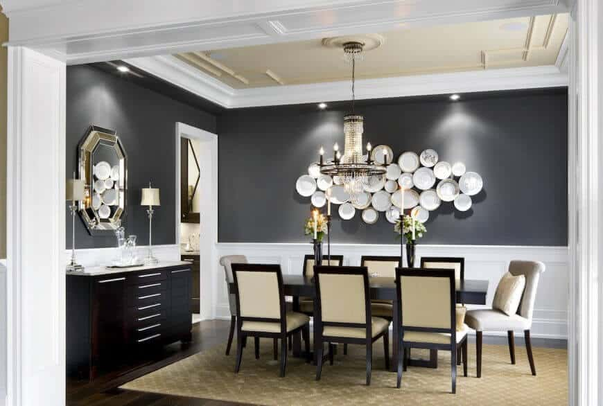 The formal dining room has white wainscoting around the bottom of the room, while the top majority of the wall is painted a dark navy. A collection of elegant china plates of different sizes and shapes are arranged on the wall behind the table as art.
