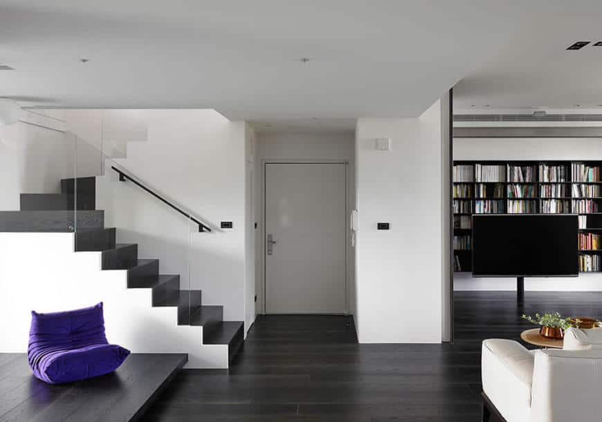 White walls were chosen as the backdrop to this stunning home remodel to allow the subtle additions of color to pop throughout the home. Black flooring is used throughout the main floor to make the entire space move from light to dark vertically.