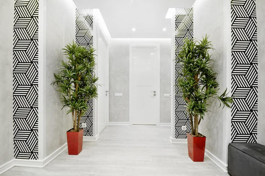 Take a look at the main entryway for the home, where high contrast geometric wallpaper offers a startling break from the white color palette.