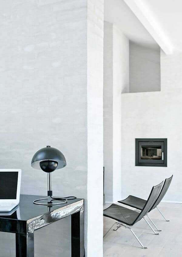 This home office has a black desk table with a table lamp. It also has a fireplace and beige carpet flooring.