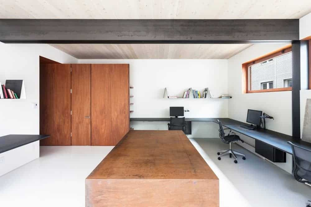 This office room has huge wooden cabinetry that match the wooden table in the middle. It also has a black desk and office chairs.