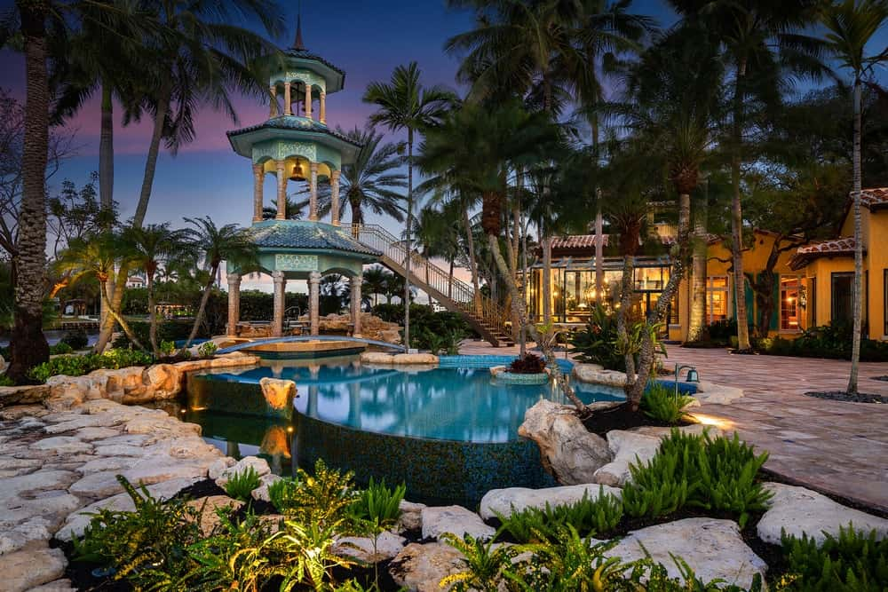 The beautiful backyard pool has a gorgeous background landscaping filled with tall tropical trees and plants. Next to the pool is a large three-story high stone structure with an outdoor dining area at the bottom and a viewing deck adorned with a large bell on the second level. Images courtesy of Toptenrealestatedeals.com.