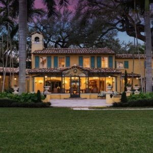 The gorgeous waterfront home has a rustic quality to its earthy beige walls augmented by the wide glass windows that emanate warm yellow lights coming from the bright interiors of the house. The house is also complemented by the surrounding lush tropical-style landscaping with tall trees and a wide lawn of grass. Images courtesy of Toptenrealestatedeals.com.