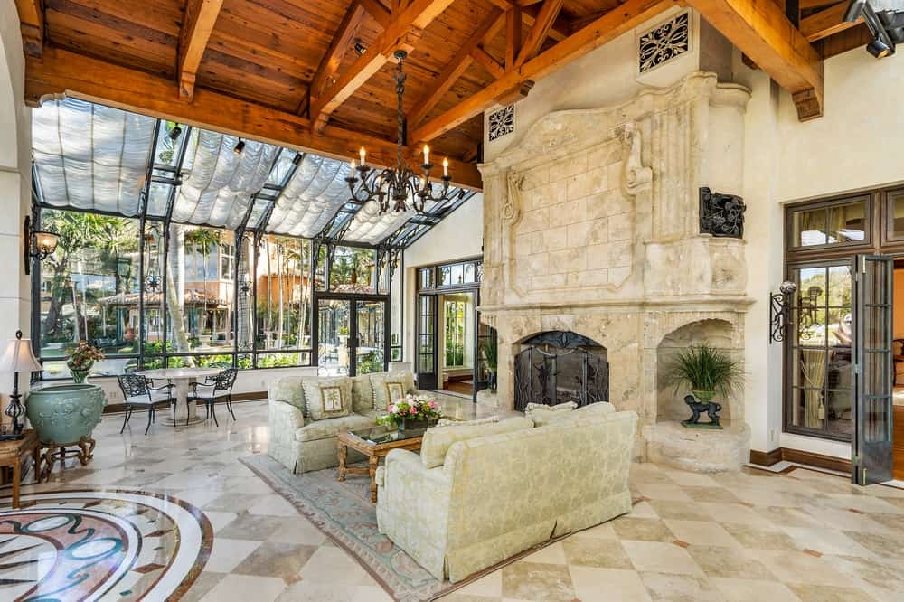 The large living room has a spacious beige marble flooring with a checkered design. This is matched with the beige pair of sofas next to the beige stone structure that houses the large fireplace. The area is complemented by the lovely wooden tall ceiling with exposed wooden beams and on the side is an informal dining area illuminated by the glass walls. Images courtesy of Toptenrealestatedeals.com.