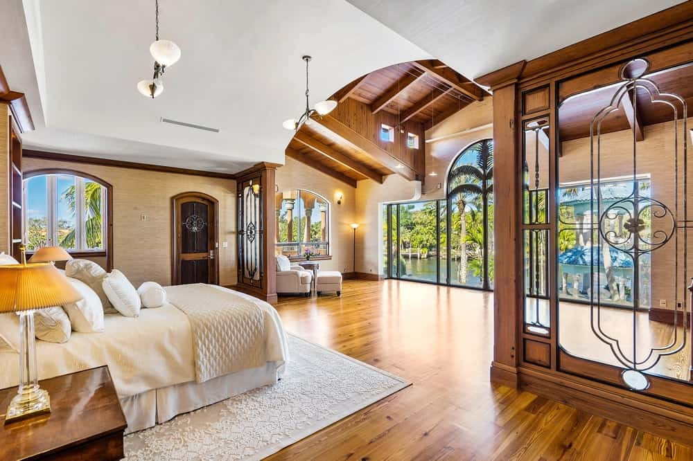 The large primary bedroom has a wide hardwood flooring that matches with the wall accents, door, arched wooden ceiling as well as the bedside drawers of the bed. These are then contrasted by the bright white bed, area rug and the ceiling directly above the bed brightened by the wide glass walls. Images courtesy of Toptenrealestatedeals.com.