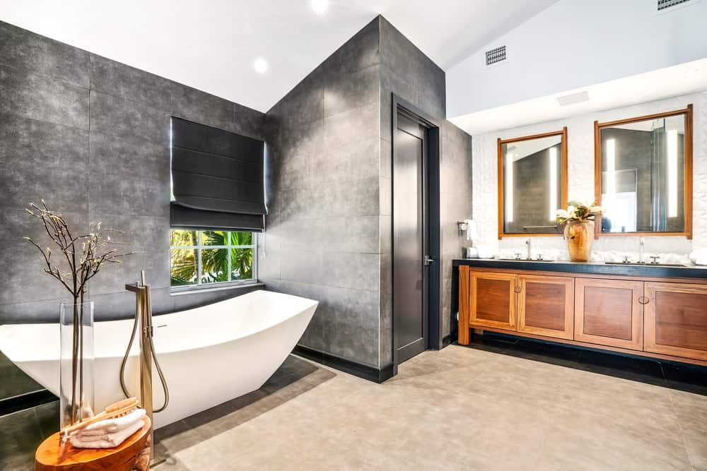 The primary bathroom has gorgeous charcoal gray tiles on its walls that gives a lovely contrast to the white shed ceiling, beige flooring tiles as well as the porcelain freestanding bathtub placed by the window with a dark shade. This bathroom also has a beautiful two-sink wooden vanity paired with wall-mounted mirrors that has wooden frames. Images courtesy of Toptenrealestatedeals.com.