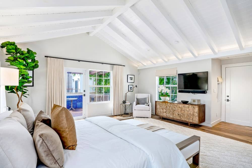 This primary bedroom has a tall and charming wooden cathedral ceiling with exposed wooden beams in a light tone to match the beige walls, white bed and the white cushioned arm chair in the corner for a lovely reading nook. The bed is adorned with a potted plant on the side and a wooden cushioned bench at the foot. Images courtesy of Toptenrealestatedeals.com.
