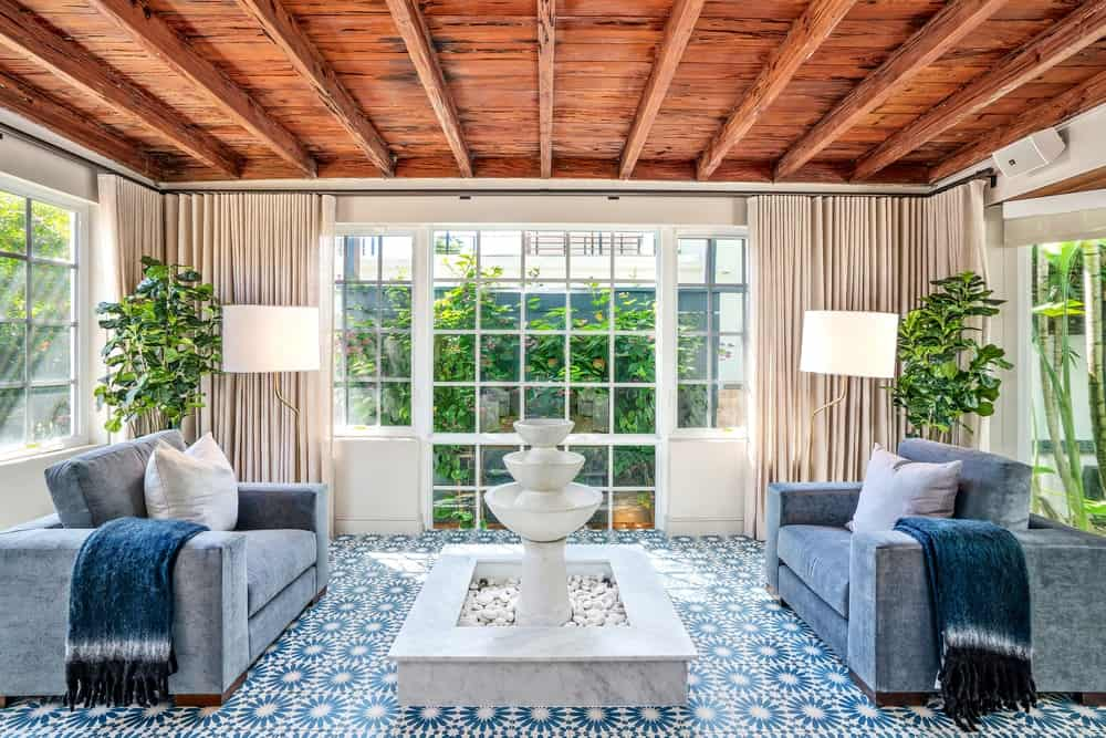 This other living room has a beach-style patio vibe to its blue patterned flooring tiles and white marble fountain in the middle of two gray sofas. These are complemented by the charming wooden ceiling with exposed wooden beams brightened by the abundant natural lighting coming in from the wide glass windows. Images courtesy of Toptenrealestatedeals.com.