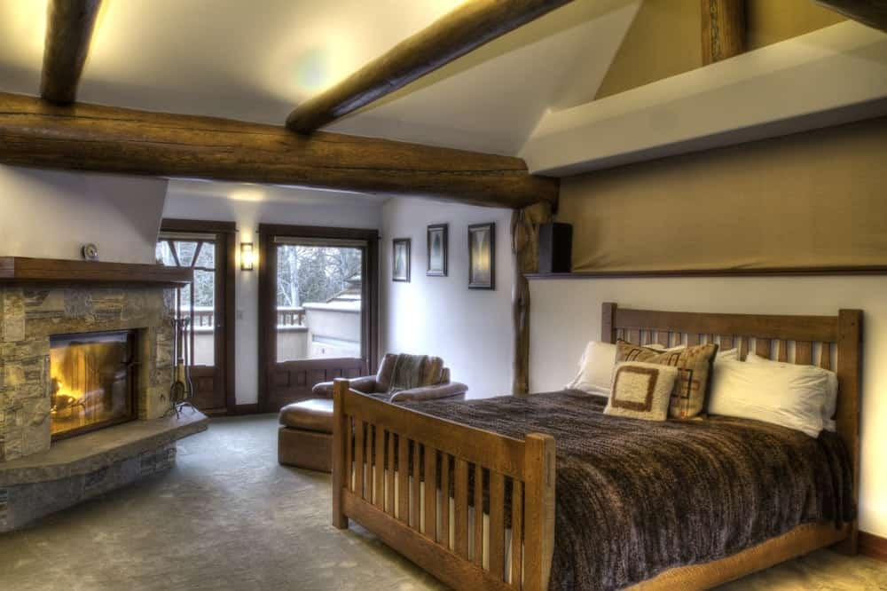 The bedroom's wooden sleigh bed is a perfect match for the wooden exposed beams of the ceiling and the wooden frames of the windows and doors that complement the beige walls and ceiling. Images courtesy of Toptenrealestatedeals.com.