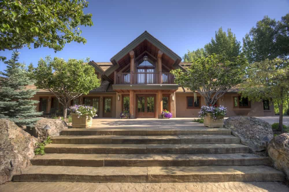 The front view of the house shows the complement of the large glass windows and doors to the wooden elements of the house that pairs well with the earthy concrete walkways. Images courtesy of Toptenrealestatedeals.com.